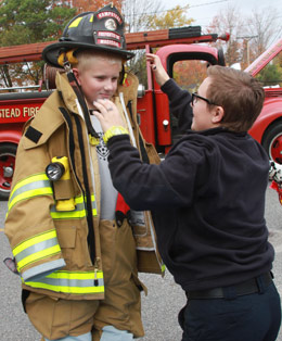 Eric Stier, 9, gets help from Firefighter/ Emergency Medical Technician Pattie MacIsaac in trying on her turnout gear. Photo by Chris Paul