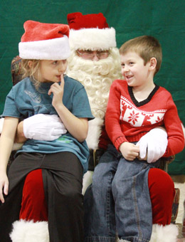 Shelby, 7, and Greg Peters, 4, divulge their Christmas gift wishes to Santa Claus during the annual Breakfast with Santa.