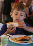 First-grader Joey Beck digs into his hotdog, cooked by the local firefighters. Photo by Chris Paul.