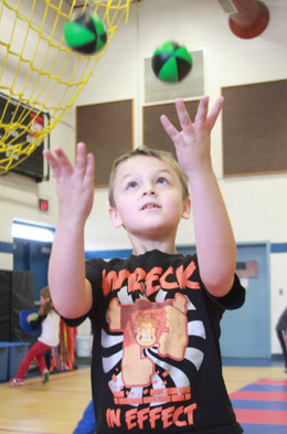 Hampstead Central School first grader Luke Thibodeau hones his skills at juggling during a practice period while being trained by artist-in-residence Troy Wunderle of Big Top Adventures. Photo by Chris Paul