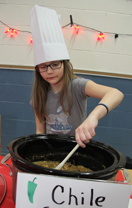 Jullianna VanGeyte stirs up her dad's entry into the annual Dads' Chili Cook Off at Chester Academy. Photo by Chris Paul.