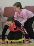 Fifth grader Paige Douglas is pushed along on a scooter by Alyssa Camell during a relay race. Photo by Chris Paul