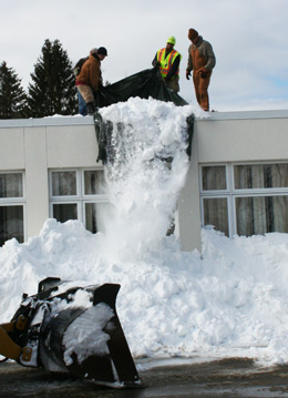 Workers with the town highway department and MLM Construction were busy shoveling multiple feet of snow off the flat and angled roofs over the most used portions of the municipal building and dumping out tarps full of snow. Photo by Matt Rittenhouse